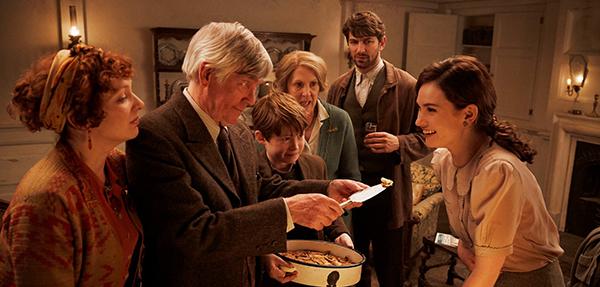 """Juliet (Lily James) probiert den namensgebenden Kartoffelschalenauflauf des """"Guernseyer Freunde von Dichtung und Kartoffelschalenauflauf"""" Buchclubs."""